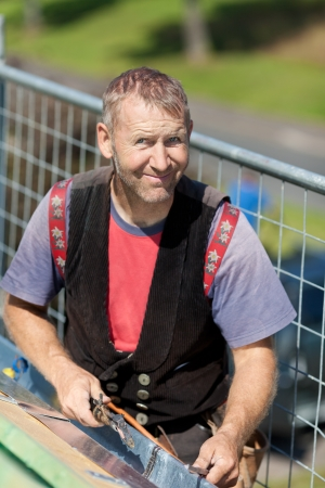 Smiling mature roofer welding the gutter on a new roof photo