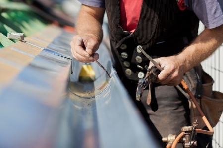 roofing: Close-up of a roofer welding the gutter on a new roof Stock Photo