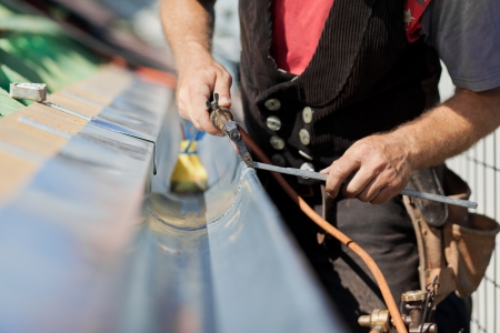 flashing: Close-up of a roofer applying weld into the gutter parts to assemble it