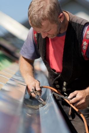 Ltere Dachdecker Anwendung Schweißnaht in die Gosse Teile, um es in eine neue Baustelle montieren Standard-Bild - 21259906