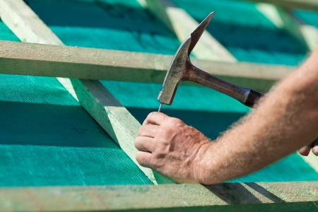 artisan: Roofer hammering a nail into the new roof beams Stock Photo