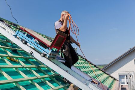 Roofer using the construction site elevator to carry material to the rooftop Stock Photo - 21259907