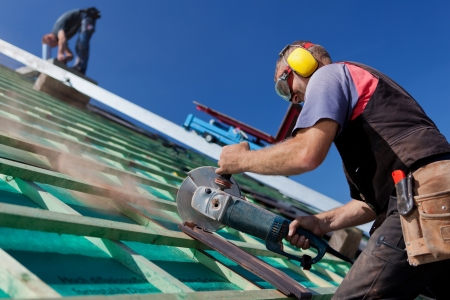 construction work: Roofer using a hand circular saw to cut a roof-tile Stock Photo