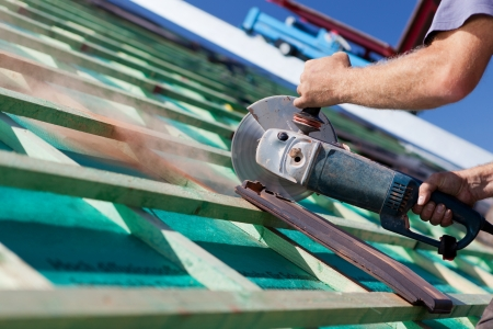Close-up of a roofer using a hand circular saw to cut a roof-tile photo