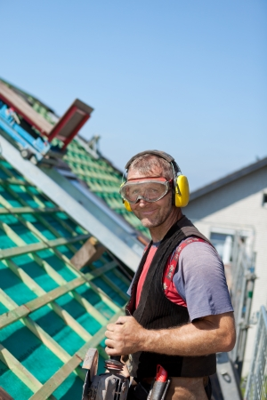 Portrait of a roofer using safety goggles, ear mufflers and holding a hand circular saw Stock Photo - 21259910