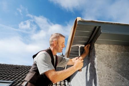 dormer: Techador trabajando en un nuevo buhardilla por clavar clavos en el borde del techo