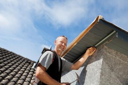 roofer: Roofer assembling parts of the dormer rooftop edge