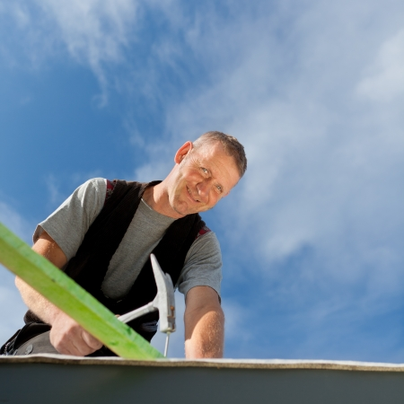 Smiling roofer hammering a nail into a roof beam on a sunny day Stock Photo - 21259914