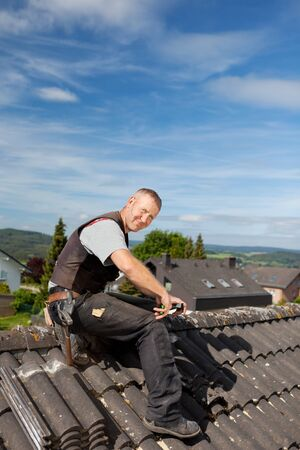 Happy roofer working on a roof tile sitting on top of a roof Stock Photo - 21259920