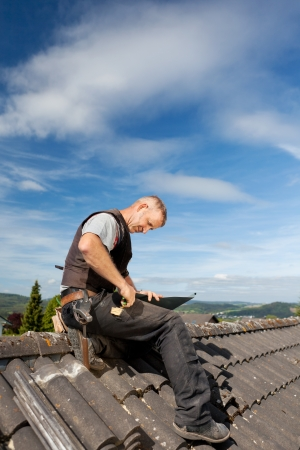 Roofer working on a metal sheet on the rooftop on a sunny day photo