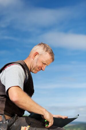 Roofer cutting a metal sheet on the rooftop with cutting pliers Stock Photo - 21259922