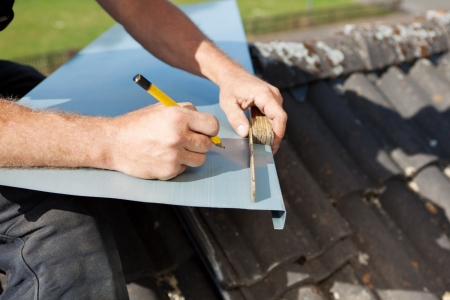 Roofer measuring and marking a metal sheet with a folding ruler and a pencil