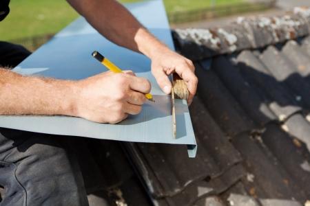 marking up: Roofer medir y marcar una hoja de metal con una regla plegable y un l�piz