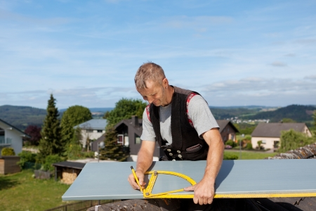 Roofer working with an angle ruler to mark a metal sheet Stock Photo - 21259923