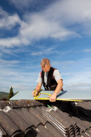 Roofer working with an angle ruler to mark a metal sheet on a rooftop Stock Photo - 21259924