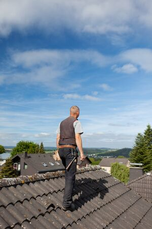 Roofer carrying tools on the rooftop on a sunny day Stock Photo - 21259946