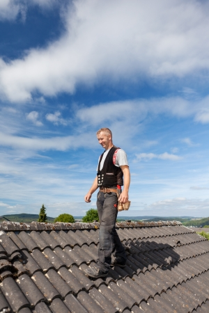 Roofer walking over an old roof on a sunny day Stock Photo - 21259948