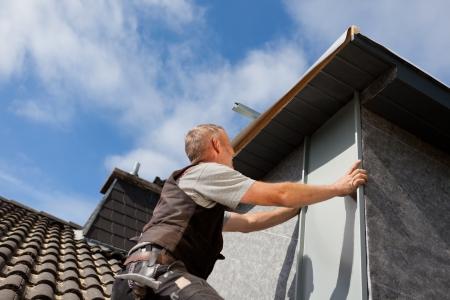 Roofer 화창한 날에 지붕창 벽에 금속 조각을 조립 스톡 콘텐츠