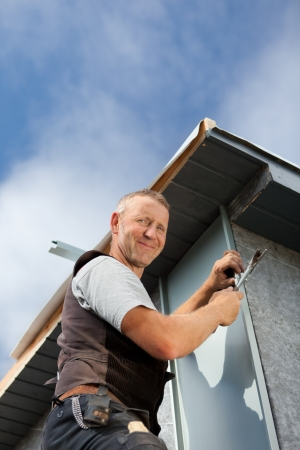 Smiling roofer assembles a metal piece on a dormer wall photo