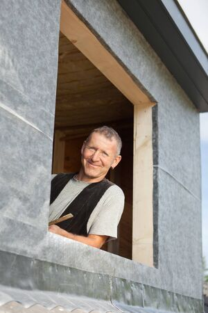 dormer: Portrait of a roofer looking through a new dormer window Stock Photo