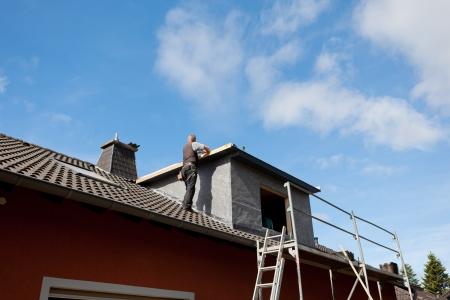 dormer: Techador trabajando en un nuevo techo buhardilla de pie en la azotea Foto de archivo