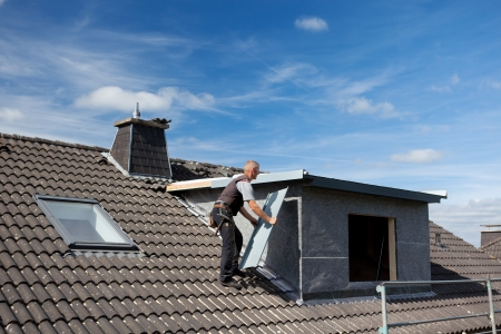 Roofer은 지붕창 벽에 옥상을 통해 금속 조각을 들고