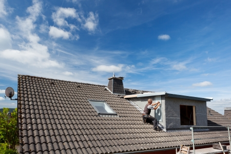roofer: View of a rooftop with a working roofer assembling pieces to the dormer wall Stock Photo