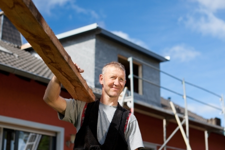 Smiling roofer carrying a wood plank over his shoulder Stock Photo - 21259962