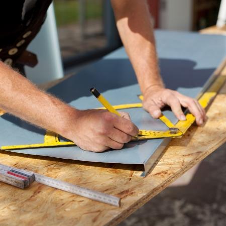 Dachdecker arbeiten mit einem Winkelmesser Markierungen auf einem Blech machen