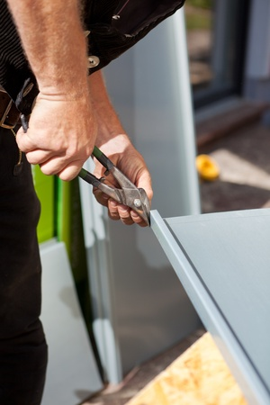 Roofer making cuts on a metal sheet using cutting pliers photo