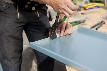 Roofer finishing folding a metal sheet using special pliers with a large flat grip
