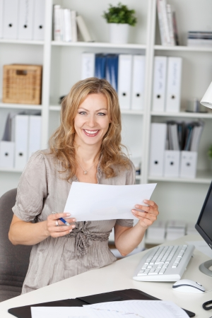Portrait of happy businesswoman holding paper while sitting on chair at office Stock Photo - 21260989