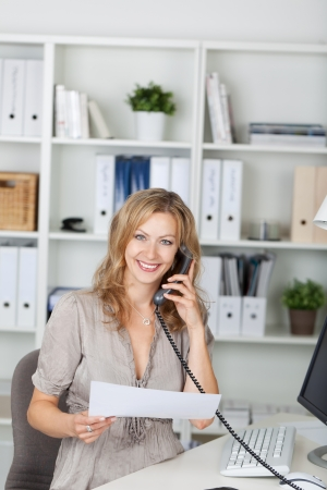 telephone receiver: Portrait of happy businesswoman holding paper while communicating on landline phone at office Stock Photo