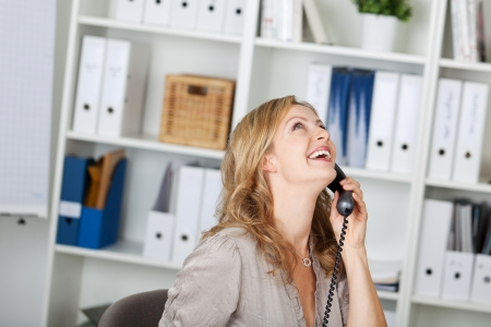waistup: Portrait of happy businesswoman communicating on land line phone at office