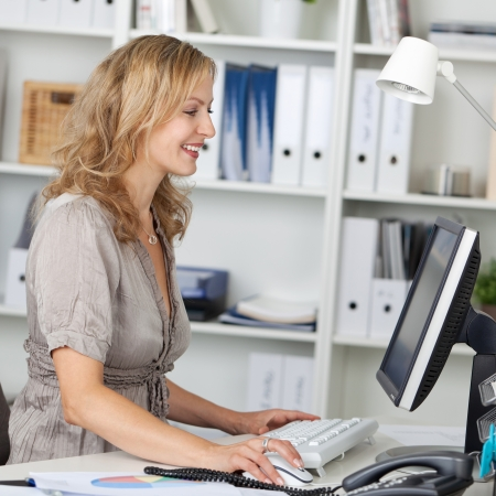 Side view of happy businesswoman using computer at desk in office Stock Photo - 21260978