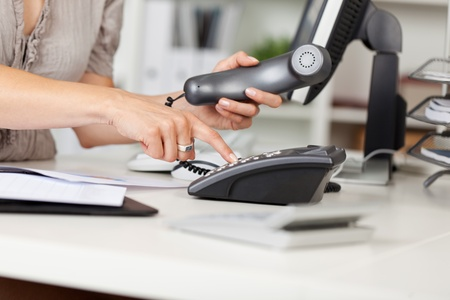 Closeup of businesswoman pressing number button at office desk photo