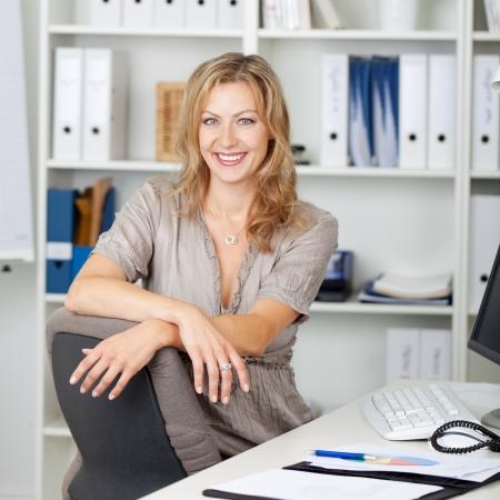 Portrait of zuversichtlich Unternehmerin sitzt am Schreibtisch im Büro
