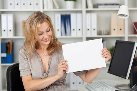 Mid adult businesswoman holding blank paper at office desk Stock Photo - 21261029