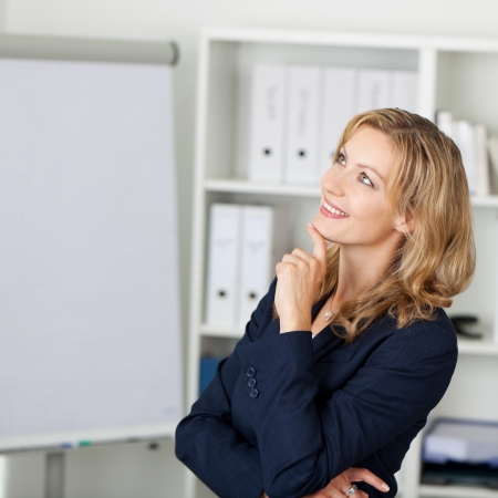 Portrait of mid adult businesswoman with hand on chin smiling in office Stock Photo - 21261031