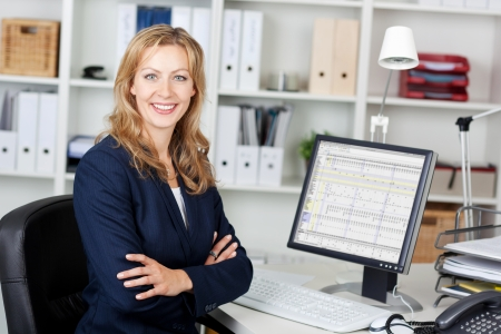 Portrait of mid adult businesswoman with computer at office desk Stock Photo - 21261037