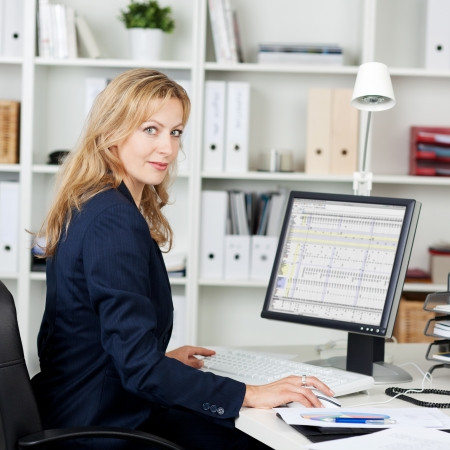 Side view portrait of mid adult businesswoman using computer at office desk Stock Photo - 21261039