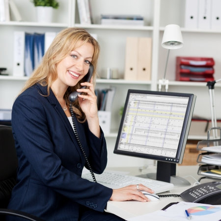 looking at computer screen: Portrait of confident businesswoman using landline phone at desk in office