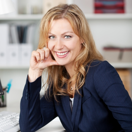 Happy mid adult businesswoman with hand on chin in office Stock Photo - 21261045