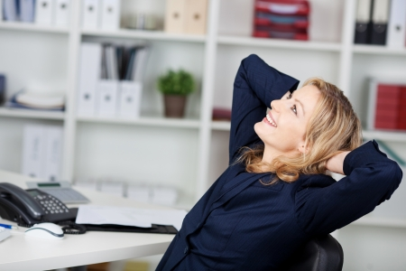 woman thinking: Happy businesswoman relaxing with hands behind head at office desk