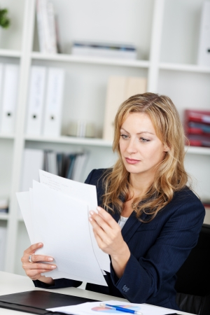 woman in suit: Mid adult businesswoman reading documents at office desk