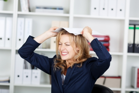clenching teeth: Angry businesswoman clenching teeth while placing documents on head in office