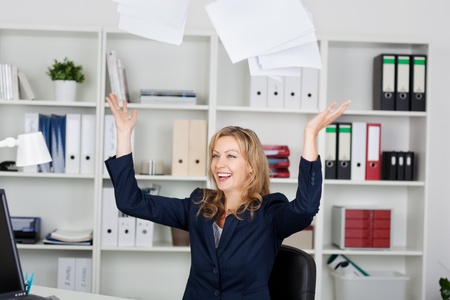 Happy mid adult businesswoman throwing documents in office Stock Photo - 21261078