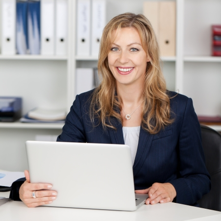Smiling mid adult businesswoman using laptop at office desk Stock Photo - 21261079