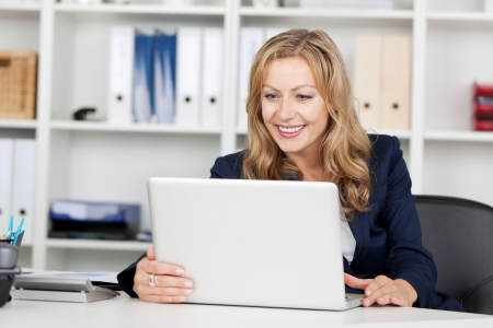 Happy mid adult businesswoman using laptop at office desk Stock Photo - 21261081