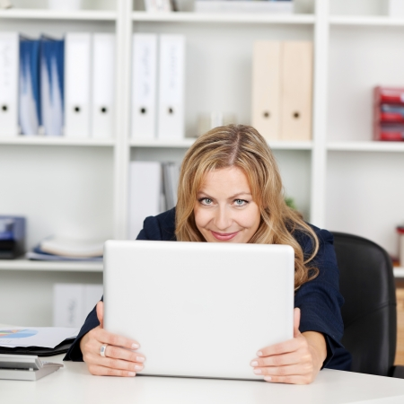 Happy mid adult businesswoman behind laptop at office desk Stock Photo - 21261083